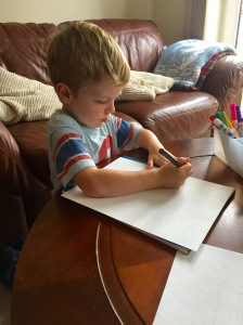 Drawing his castle with pencil to start